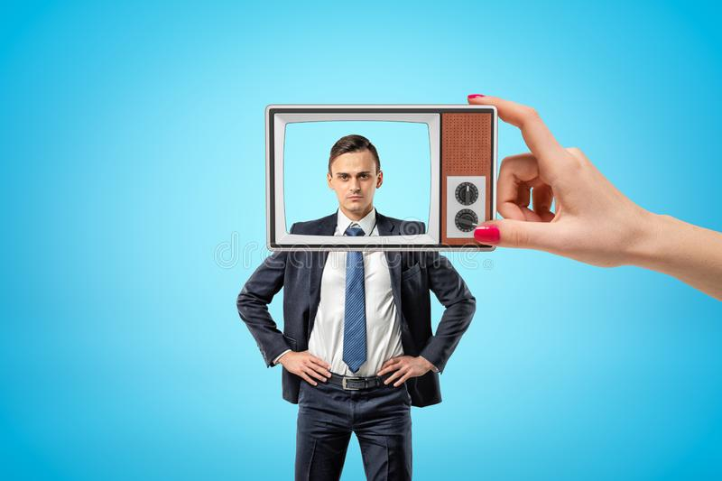 Young serious businessman standing, hands on hips, looking at camera through old TV frame with removed screen, held in. Woman`s hand. Self-presentation. Huge stock photo