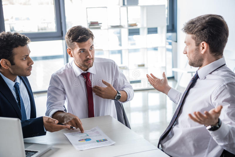 Young serious businessmen working with charts and graphs in office stock photos