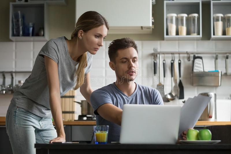 Young serious couple discussing domestic bills with papers and l. Young serious couple discussing papers with laptop, men and women roommates or husband and wife royalty free stock images