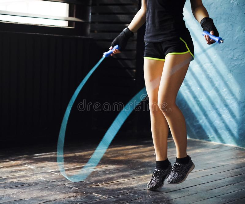 Young serious female boxer in wrapped hands warming up, jumping on skipping rope in gym. Fit woman preparing to boxing competition. Wellness, fighting stock photos