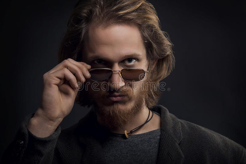 Young serious man with beard and moustache looking over his sunglasses stock photo