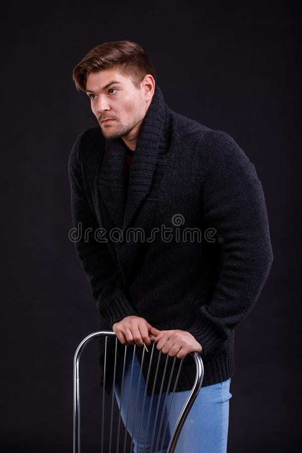 A young, serious man on a black background, leaning on a chair stock photos