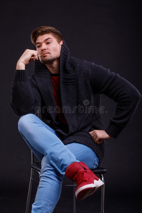 A young, serious man on a black background, sits on a chair, with a match in his mouth, putting his foot on his leg royalty free stock images