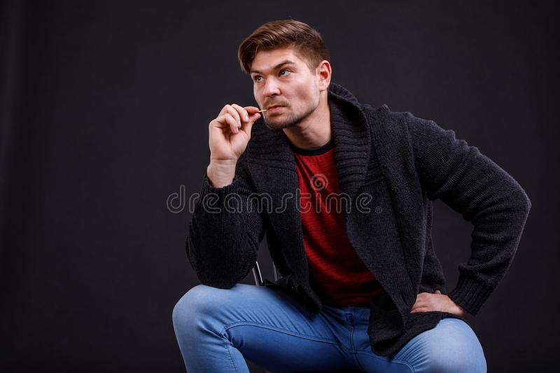 A young, serious man on a black background, sits, with a toothpick in his mouth. royalty free stock photography