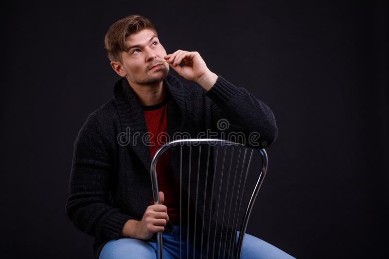 A young, serious man on a black background, sitting on a chair, with a match in his mouth stock images
