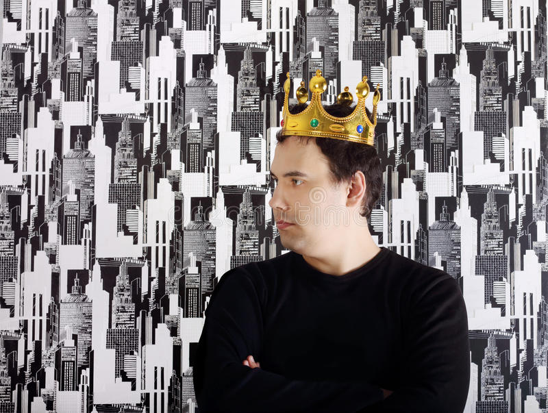 Young serious man in black shirt and gold crown royalty free stock image