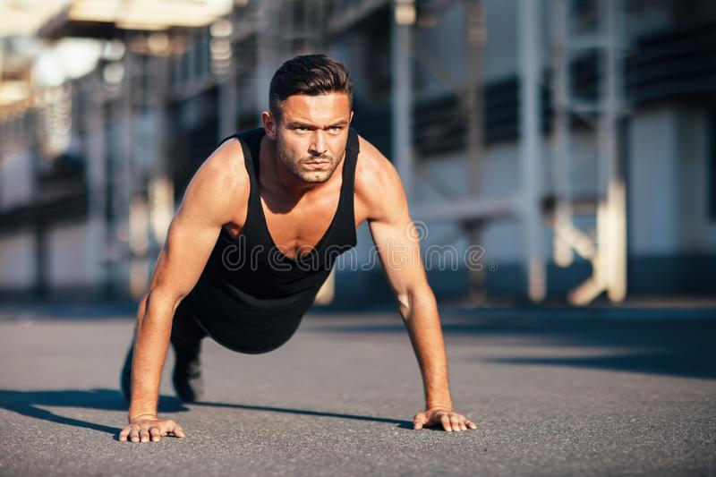 Young serious man doing pushups outdoor on industrial background royalty free stock images
