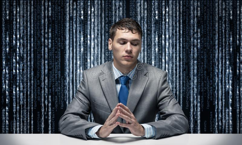 Young serious man folded hands and sitting at desk royalty free stock photos