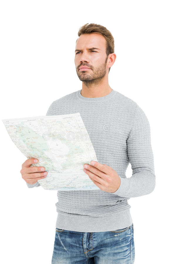 Young serious man holding a map. On white background royalty free stock photo