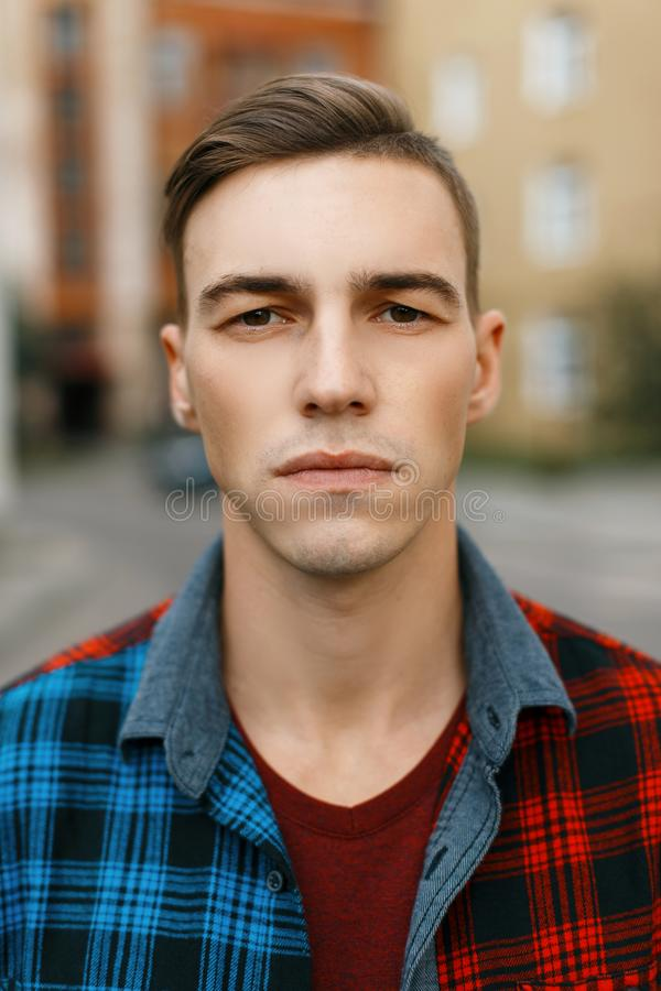 Young serious man with a stylish hairstyle in a fashionable t-shirt in a trendy plaid shirt walks around the city. Near the old brick buildings on a summer day royalty free stock photography