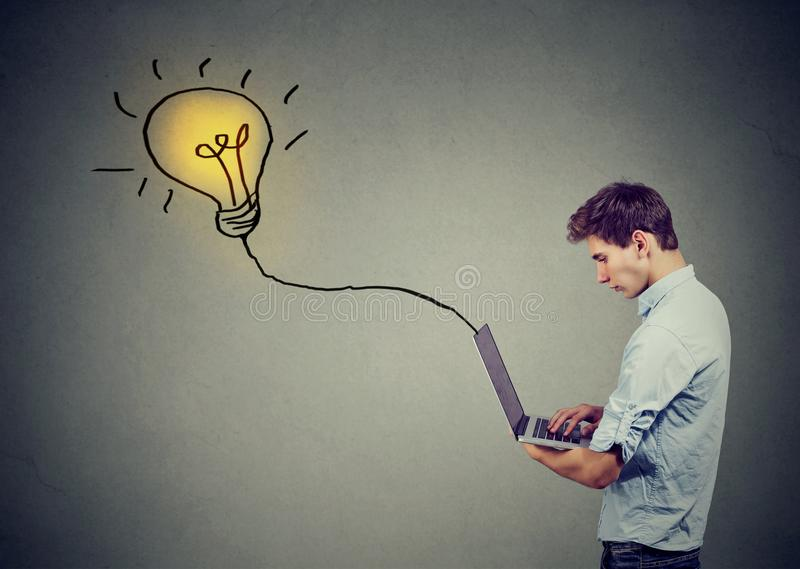 Young serious man using a laptop with light bulb plugged in it stock photos