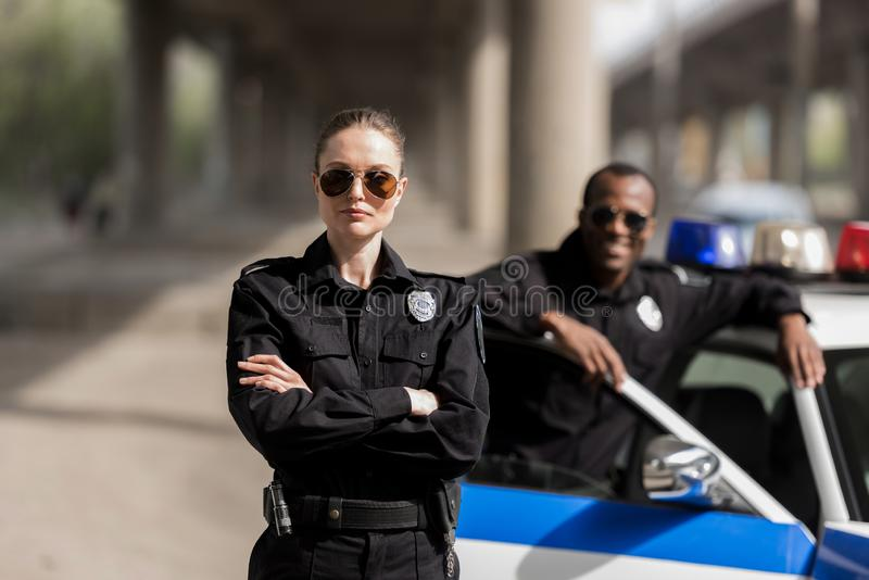 young serious policewoman standing with crossed arms while her partner standing near car and smiling blurred stock photo