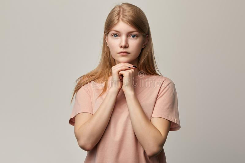 Young serious sad unhappy girl pleading over gray background stock photography