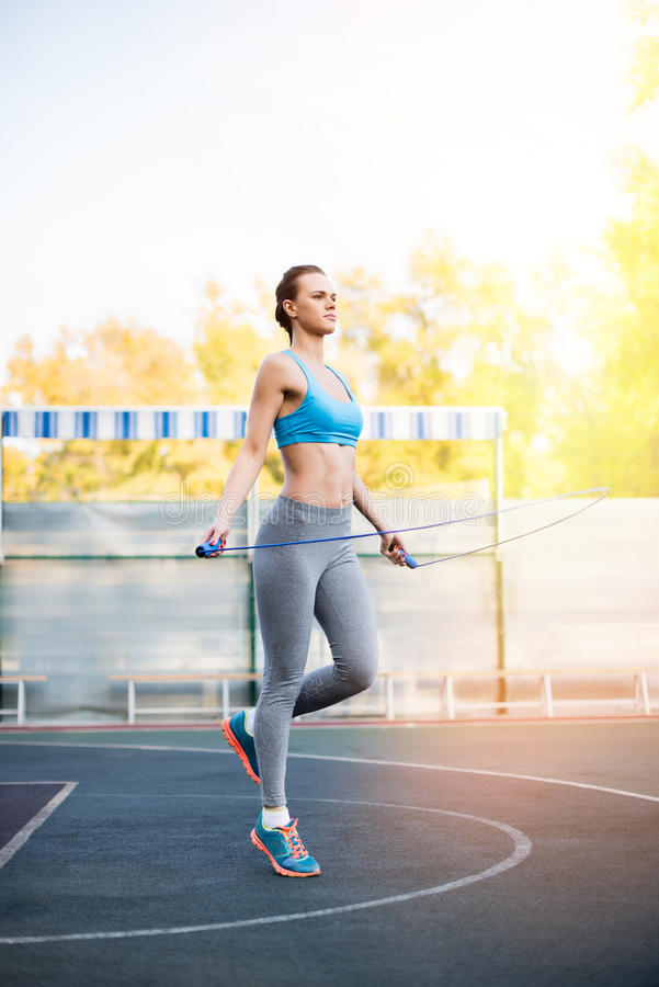 Young serious sportswoman exercising with skipping rope on stadium stock photos