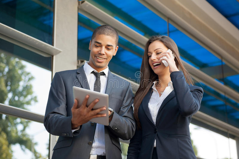young serious successful businessmen with tablet computer talking about work, outdoors stock photo