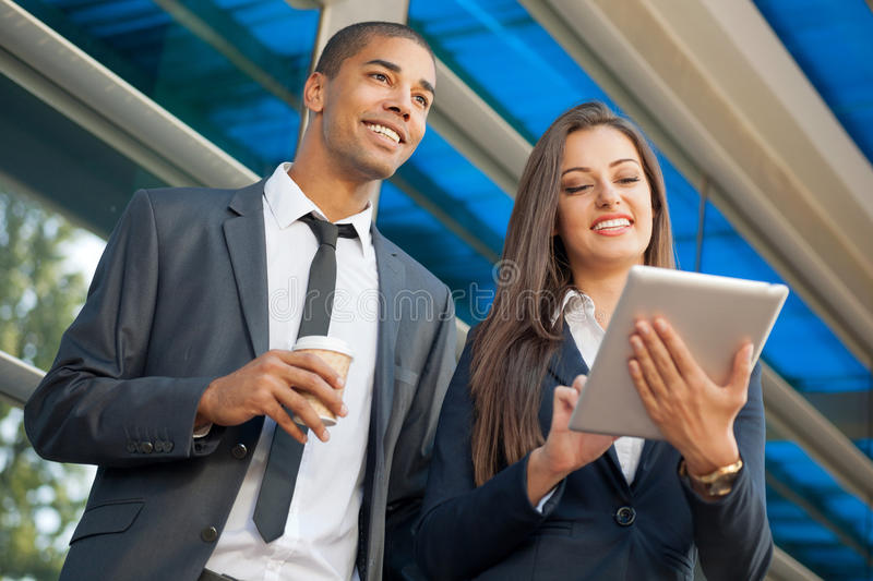 Young serious successful businesswoman with tablet computer talk stock photo
