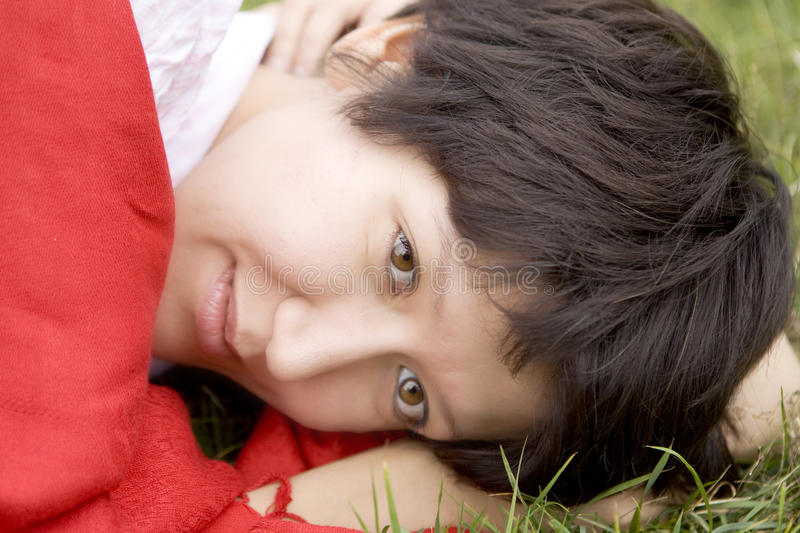 Young serious woman in red scarf lying on grass royalty free stock image