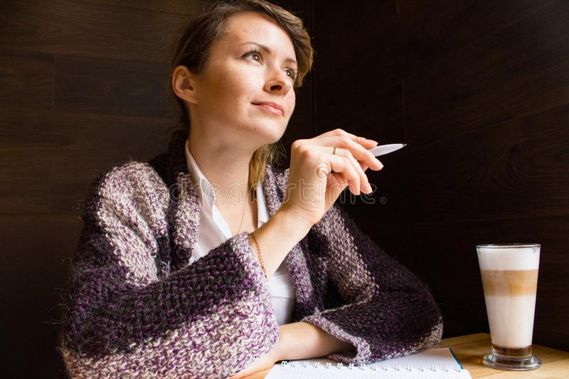Young serious woman thinking with pen and open notebook. Thoughtful girl portrait. Journalist and writer concept. Business lifesty royalty free stock images