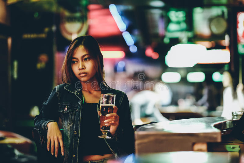 Young adult girl in a club drinking beer alone. Adult girl in a bar drinking beer royalty free stock image