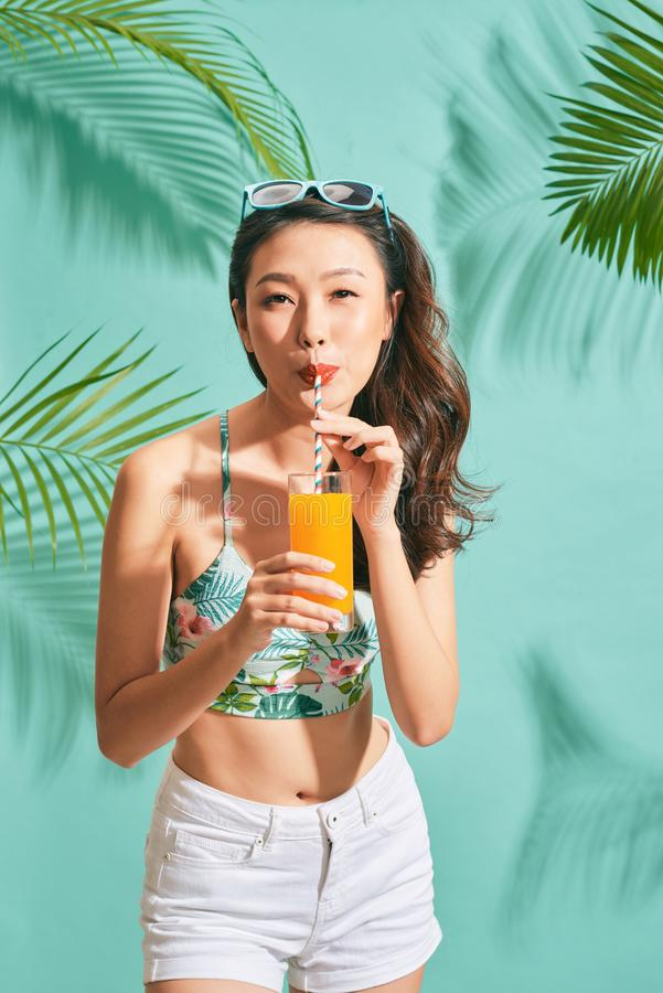 Young sexy asian woman in mini denim shorts drinking tasty juice on summer time.  royalty free stock image