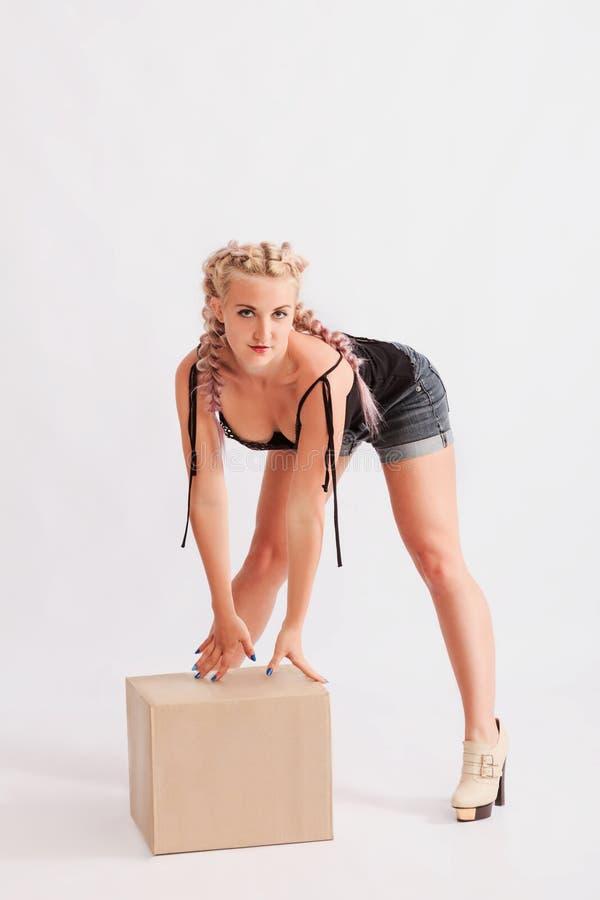 Young beautiful girl model posing next to a cardboard box royalty free stock photos