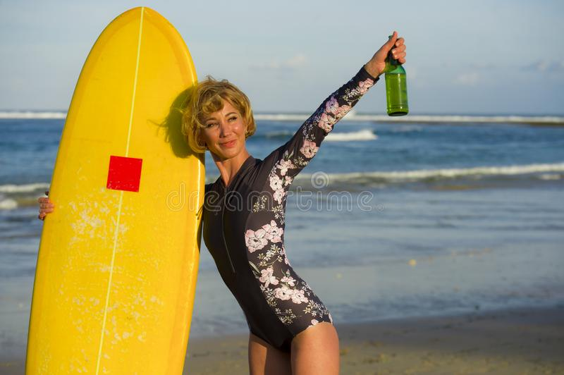 Young beautiful and happy surfer woman holding yellow surf board smiling cheerful drinking beer bottle enjoying summer holida royalty free stock photography