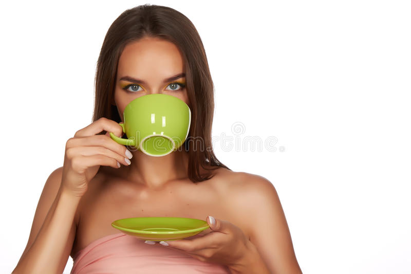 Young beautiful woman with dark hair picked up holding a ceramic cup and saucer pale pink drink tea or coffee on a white back. Ground royalty free stock photo