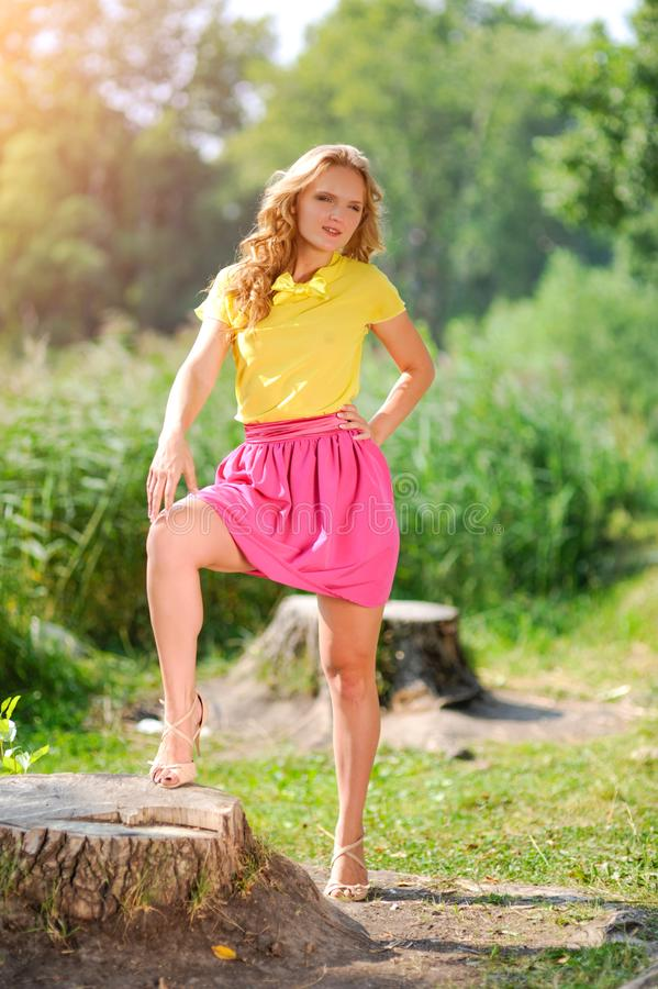 Young blonde girl in a yellow blouse with a bright pink skirt posing in a summer park in the rays of a bright sun stock photos