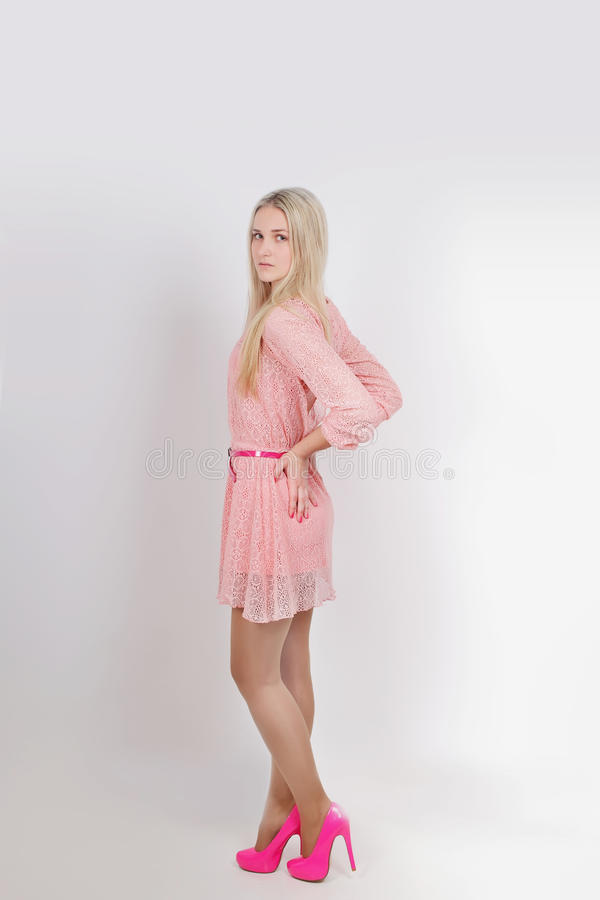 Young blond in pink dress. Studio. Vertical royalty free stock photo