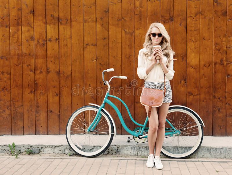 Young blonde girl with long hair with brown vintage bag in sunglasses standing near vintage green bicycle and holding a cup o royalty free stock image