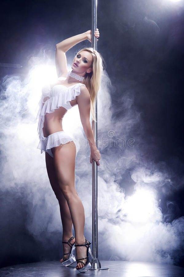 Young blonde pole dance woman. Young pole dance woman in smoke royalty free stock photo