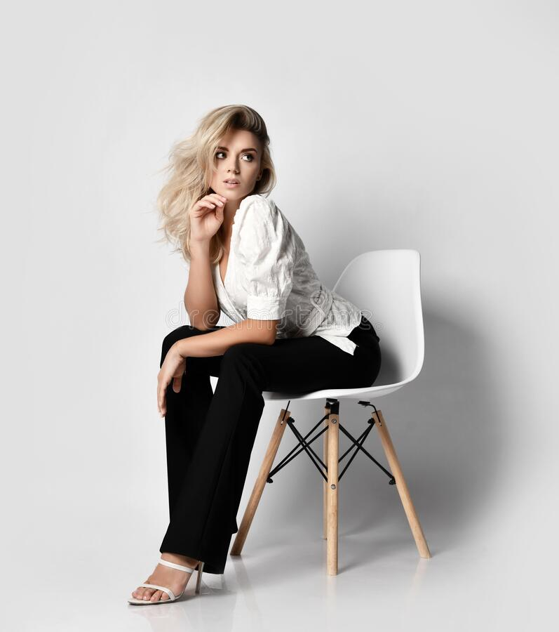 Free Young Sexy Blonde Slim Woman In Office Pantsuit Shirt And Pants Sits On Chair Leaning Forward And Looks Aside Stock Images - 196820794
