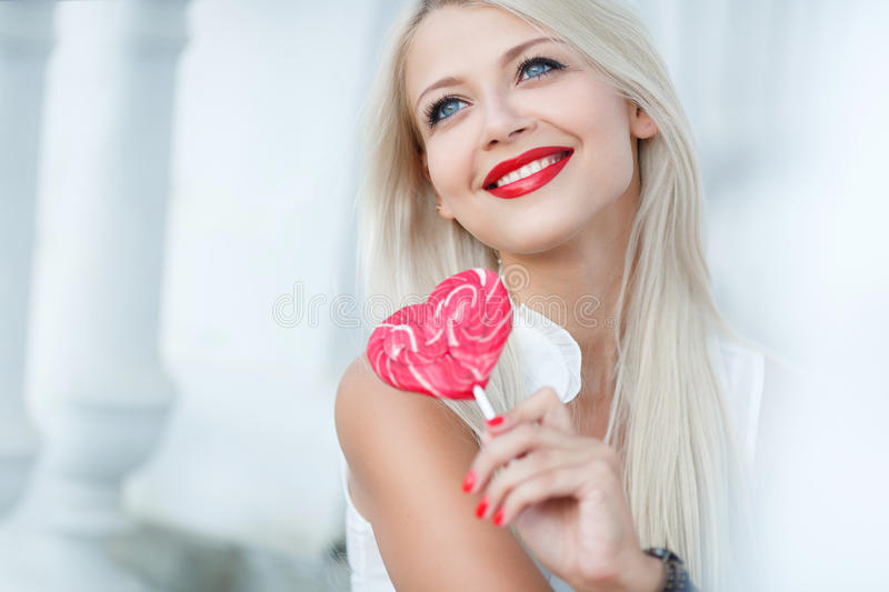 Young blonde woman with heart shaped lollipop. Portrait of a glamourous beautiful woman holding lollipop royalty free stock photography