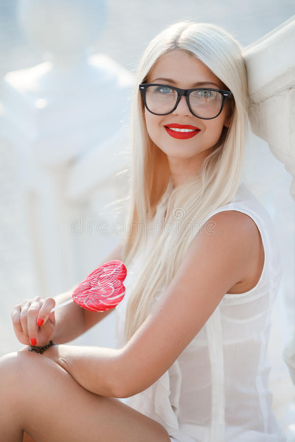 Young blonde woman with heart shaped lollipop. And sunglasses. Outdoor royalty free stock photography