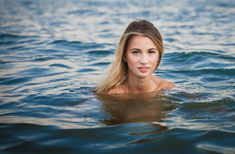 Young blonde woman swimming in ocean with Perfect hair and royalty free stock images
