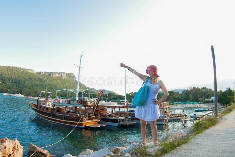 Young blonde woman in white dress near sea nad yachts. In marina stock images