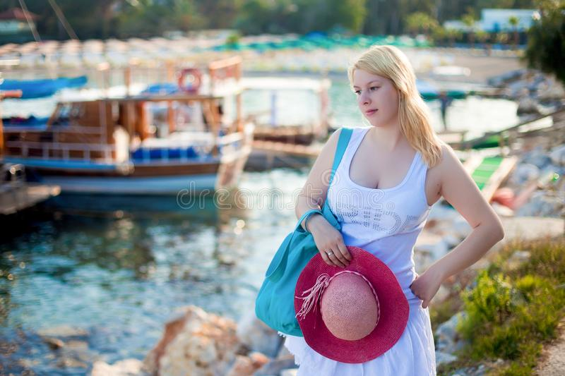 Young blonde woman in white dress near sea nad yachts. In marina stock photos