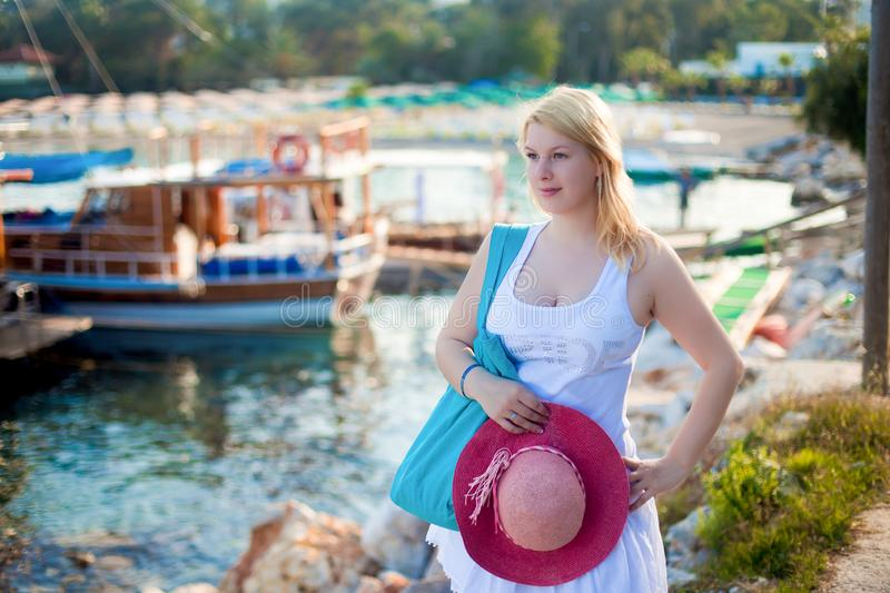 Young blonde woman in white dress near sea nad yachts. In marina royalty free stock images