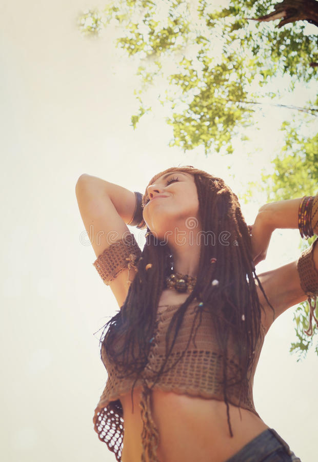 Young boho style woman enjoy sunny day relaxing in summer park, hands up and smiling royalty free stock photography