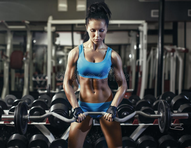 Young brunette girl in the gym doing biceps exercise with barbell stock images