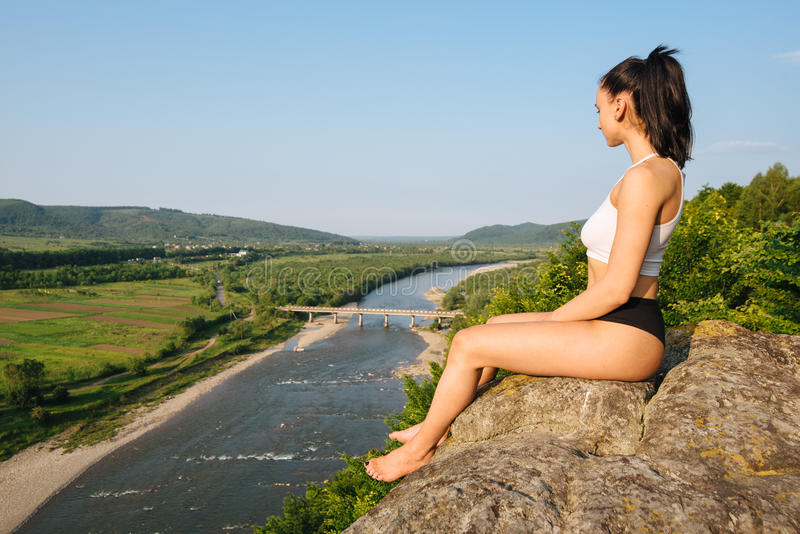 Young brunette girl with muscular body relaxing outdoor in beautiful mountains landscape. Meditation and Relax. Young brunette girl with muscular body relaxing stock photo