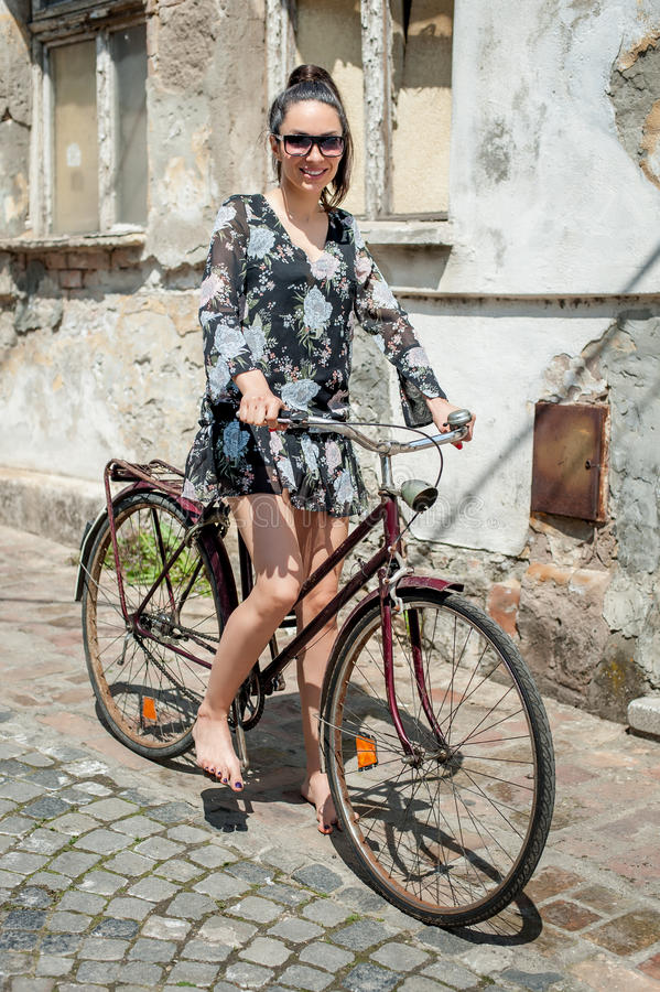 Young brunette girl with old retro style vintage bicycle stock images