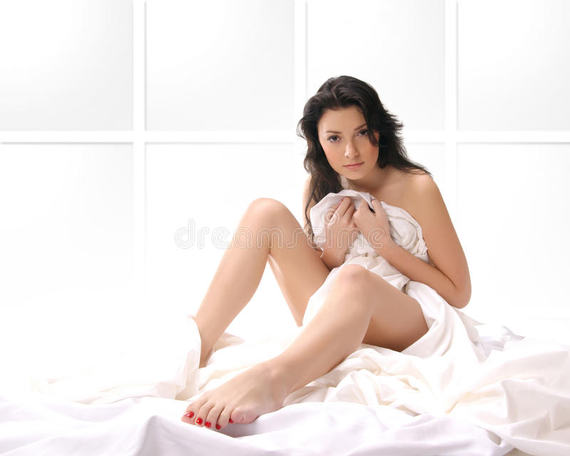 Download A Young And Brunette Sitting On A Silk Bed Stock Image - Image: 14224425