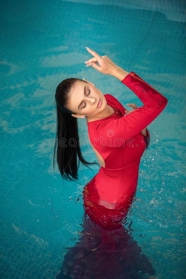 Young sexy woman floating on swimming pool in red dress. beauty shot stock photography