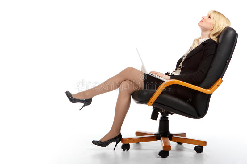 The young business woman. The young blonde the business woman sits in armchair and holds a computer royalty free stock images