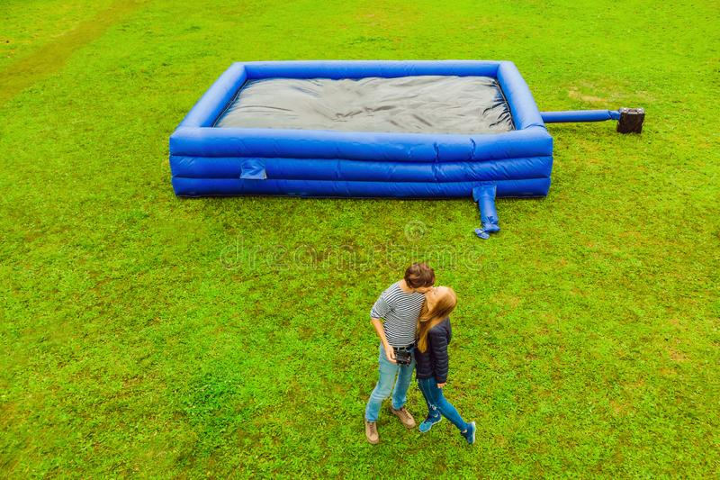 Young couple on the background of a large inflatable blue trampoline on green grass royalty free stock photography