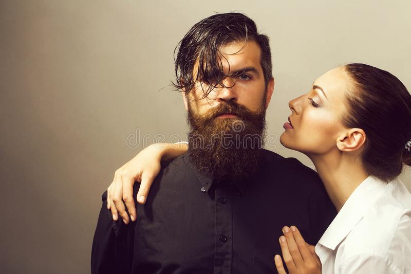 Young stylish sexy couple in studio. Young sexy couple of women with glamour makeup on pretty face in stylish shirt and bra near handsome bearded men with long royalty free stock photo