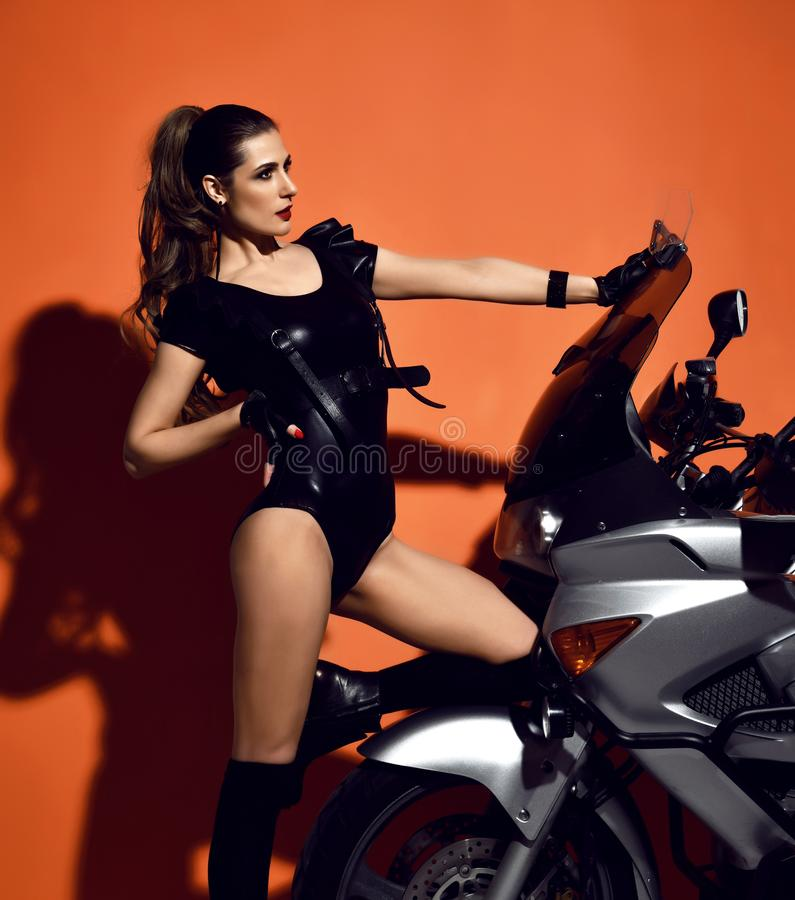Young fashion woman sitting posing on motorcycle in studio royalty free stock image