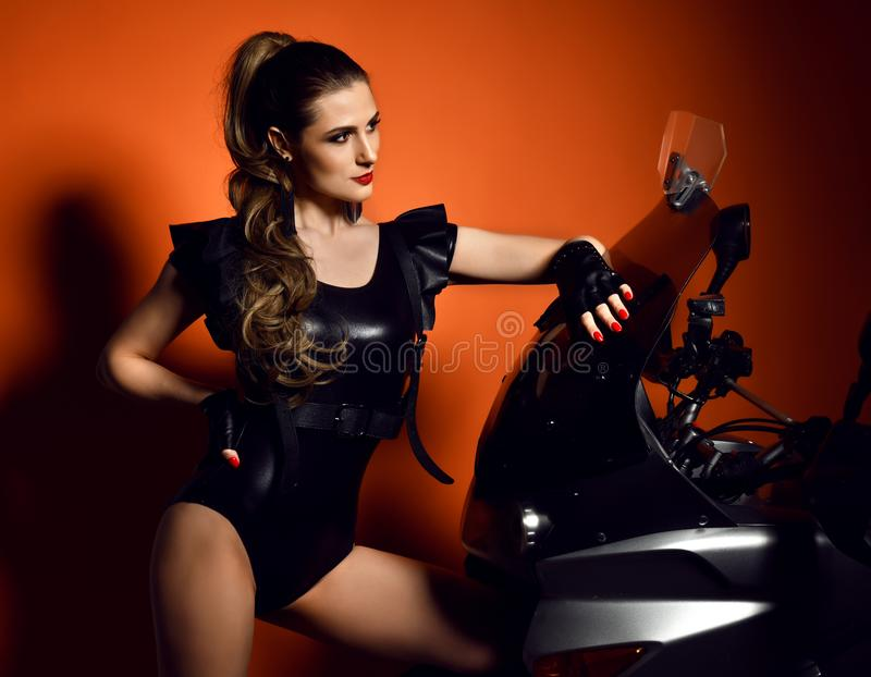 Young fashion woman sitting posing on motorcycle in studio stock photography