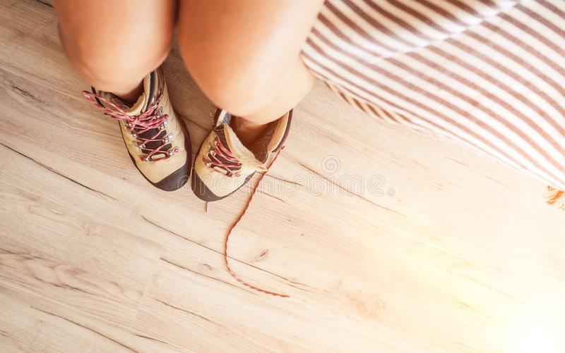 Young sexy female putted on a New trekking boots with untying laces top view in the bright sunlight morning new day. New active royalty free stock image